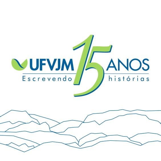 Cartão, com fundo branco, mostra na parte central, nas cores azul e verde, os dizeres: UFVJM 15 anos escrevendo histórias, antecedidos pela logomarca da universidade. Esse é o slogan da campanha que celebra o aniversário da UFVJM. Abaixo tem um desenho formado por linhas azuis que faz menção a montanhas.