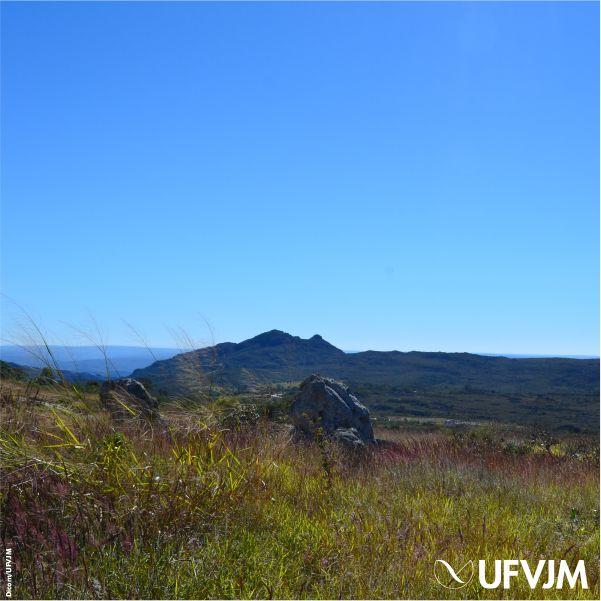 Fotografia mostra uma paisagem com céu azul sem nuvens, montanhas ao fundo e, à frente, uma vegetação rasteira com pedras. No canto inferior esquerdo está a assinatura da Dicom e, no direito, a logomarca da UFVJM.